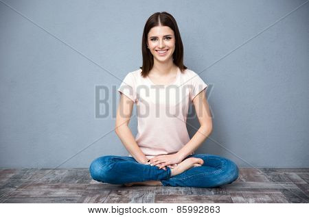 Happy young woman sitting on the floor with crossed legs