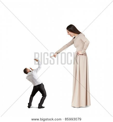 angry woman in long dress screaming at small startled man. isolated on white background