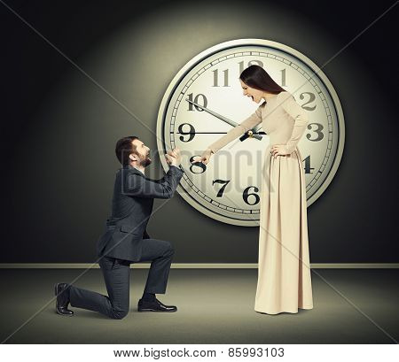 angry yelling woman pointing finger at crying man in dark room with big clock on the wall