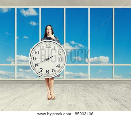 amazed woman with big white clock in empty room