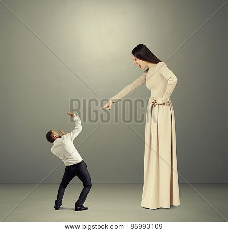 angry woman in long dress screaming at small startled man in the dark room