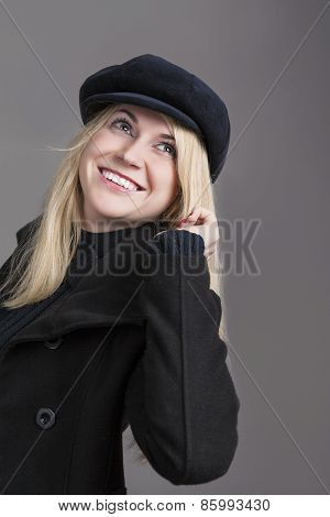 Portrait Of Happy Smiling Caucasian Woman Wearing Winter Warm Clothes. Against Gray Background