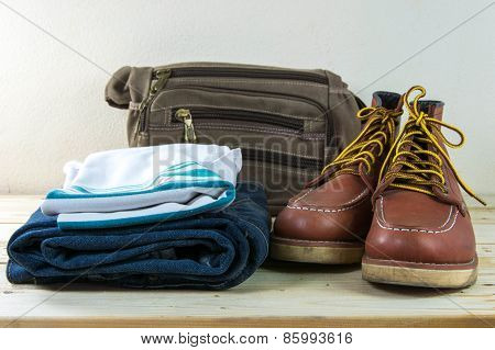 Still Life With Plaid Shirt, Jeans, Brown Boots And Bag On Wooden Table Background.