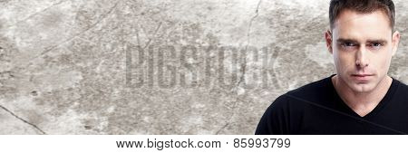 Handsome young man portrait over vintage wall background.