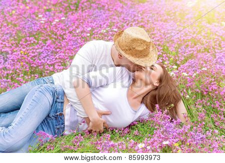 Happy couple spending time outdoors, lying down and hugging on beautiful pink flower field, romantic relationship, love and happiness concept