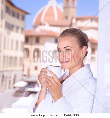 Portrait of beautiful calm woman drinking coffee in hotel room in Florence, Italy, Europe, standing on balcony on wonderful cityscape background