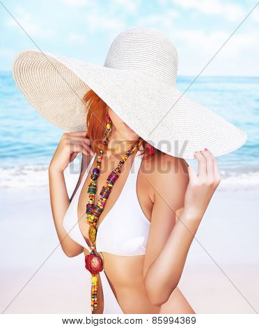 Sexy woman on the beach, fashion model posing on seashore, wearing a big hat, and covers her face, fashionable summer photo shoot