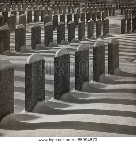 Identical soldier graves and their shadow  during winter season in black and white.