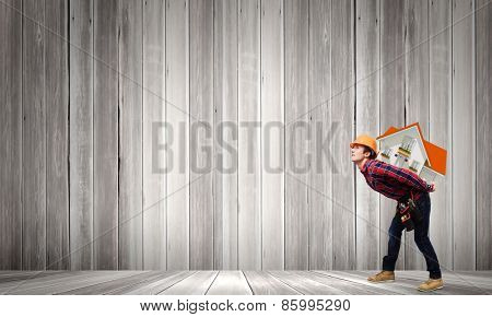 Young smiling craftsman carrying house model on back