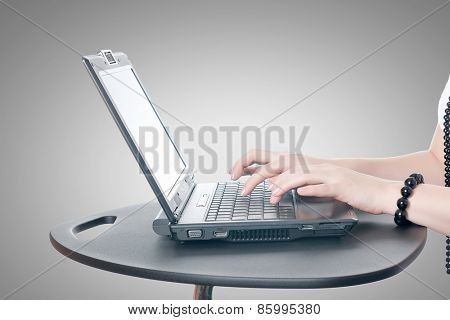 Close up of woman's hands using laptop and splashes out of monitor