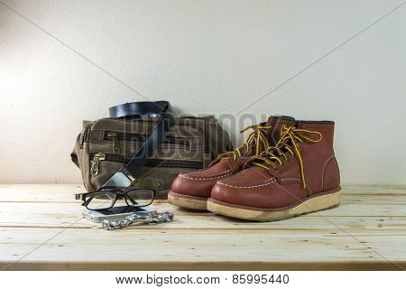 Still Life With Casual Man, Boots And Bag On Wooden Table Background.