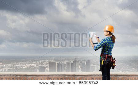 Rear view of woman engineer making some notes and sketches