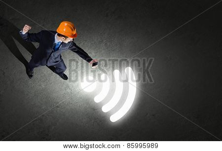 Top view of businessman in hardhat using mobile phone
