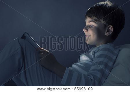 Cute boy sitting in bed and using tablet pc