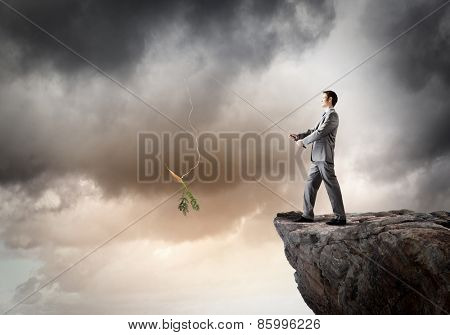Businessman standing on rock and fishing with rod