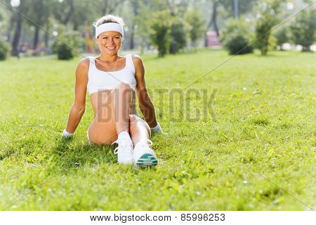 Young attractive sport girl in park sitting on grass