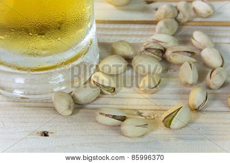 Still Life With Pistachios And Beer In A Glass On Wooden Table Background.