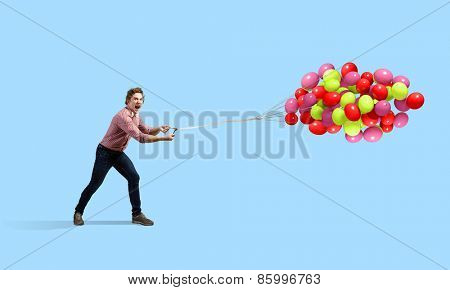 Young man in casual with bunch of colorful balloons