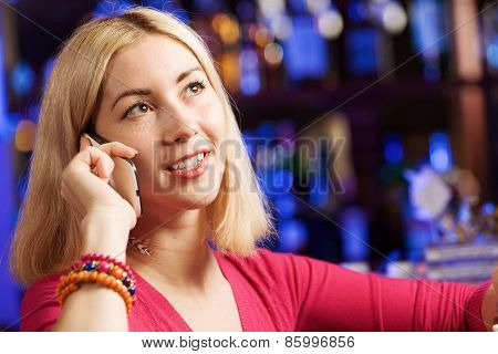 Young attractive lady at bar talking on phone