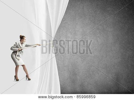 Young businesswoman pulling curtain with rope. Place for text