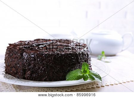 Tasty chocolate cake with cup of tea on table close up