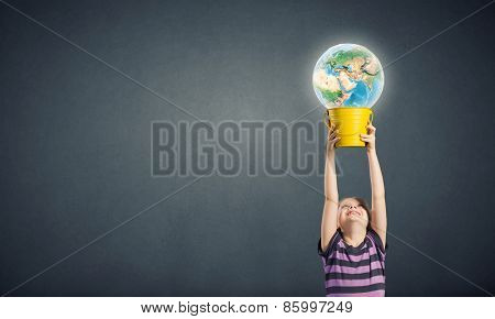 Cute girl looking at Earth planet in her bucket. Elements of this image are furnished by NASA