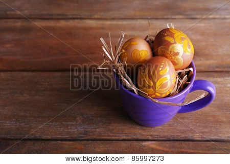 Easter eggs in mug on wooden background