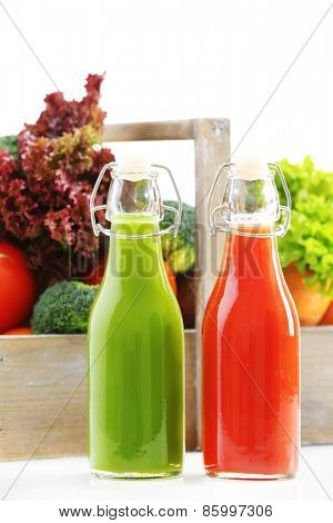 Glass bottles of fresh healthy juice with set of fruits and vegetables isolated on white background