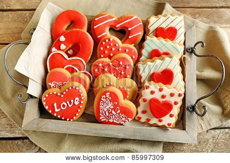 Heart shaped cookies for valentines day on tray, on wooden background