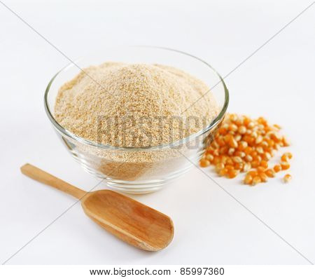 Glass bowl with flour and corn grains isolated on white