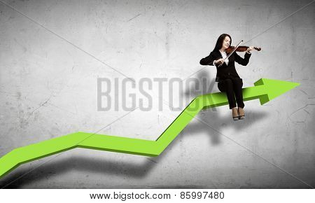 Young businesswoman sitting on increasing graph and playing violin