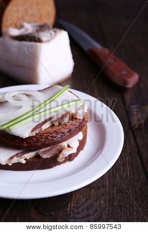 Sandwiches with lard on plate on wooden background