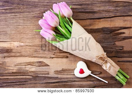 Beautiful pink tulips in paper with sweet heart on wooden background