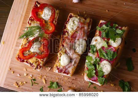 Different sandwiches with vegetables and cheese on cutting board close up