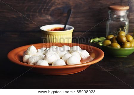 Mozzarella cheese with olives and sauce on wooden background
