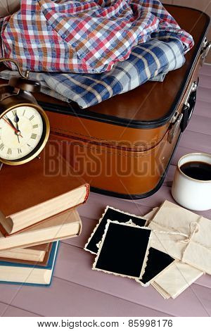 Vintage suitcase with clothes and books om wooden background