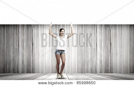Young pretty girl in shorts holding white blank banner