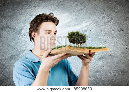 Young man in casual holding opened book with green tree