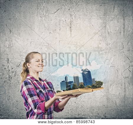 Young woman in casual holding opened book with city model