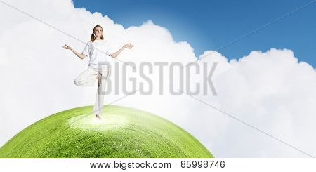 Young smiling girl standing in yoga pose