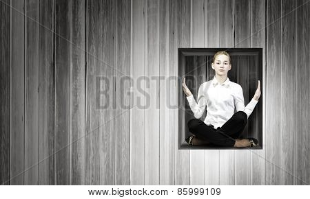 Young woman trapped in wooden cube in wall