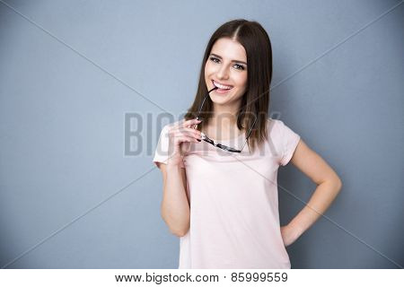 Happy young woman with glasses over gray background