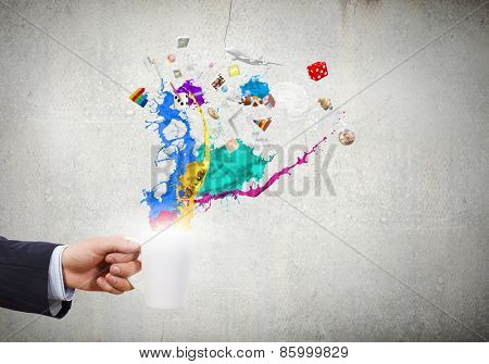 Close up of businessman holding white cup with icons flying out