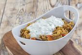 pic of curry chicken  - Bowl with curry flavored rice chicken and vegetables with garlic yoghurt sauce on rustic wooden table