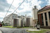 image of silos  - Industrial silos in a factory under blue sky - JPG
