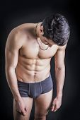 stock photo of men underwear  - Handsome fit young man wearing only underwear standing on black background looking down - JPG