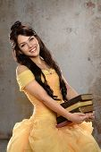 pic of dungeon  - Young  woman dressed in princess costume holding books in old room - JPG