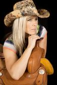 stock photo of cowgirls  - A cowgirl looking off to the side leaning on her saddle - JPG
