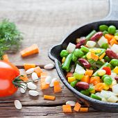 image of lenten  - Mixed vegetable meal in old frying pan closeup and ingredients on wooden rustic table - JPG