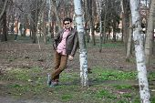 stock photo of early-man  - young man walks in the early spring in a lush park - JPG